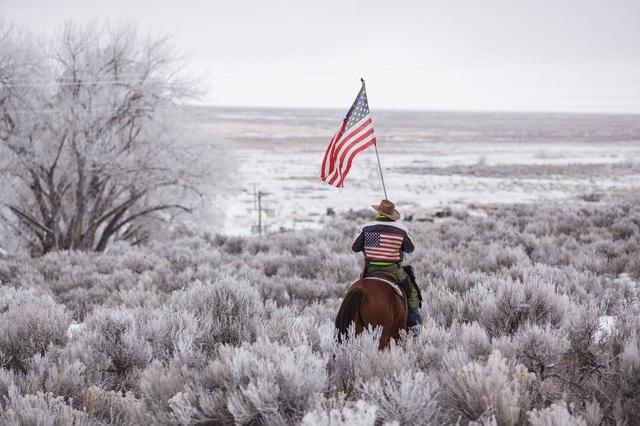Duane Ehmer cưỡi ngựa và cầm cờ Mỹ tại công viên hoang dã quốc gia Malheur, nơi bị những người biểu tình chiếm đóng ở Burns, bang Oregon hồi tháng 1. (Ảnh: AFP)
