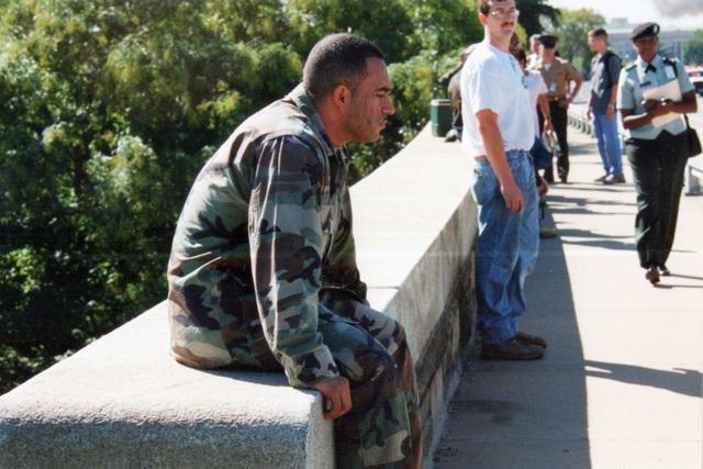 Khuôn mặt một binh sĩ phủ đầy bụi ngồi trên thành cầu gần Lầu Năm Góc đang bốc cháy. (Ảnh: Erica E. Lusk)