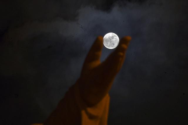 Siêu trăng nhìn qua bàn tay một bức tượng lớn. Độ sáng của siêu trăng cũng hơn bình thường khoảng 30%.