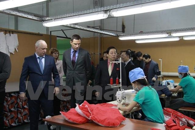 Đại sứ Nguyễn Thanh Sơn và Phó Tỉnh trưởng Moskva đi thăm các xưởng may. (Ảnh: Dương Trí/Vietnam+)