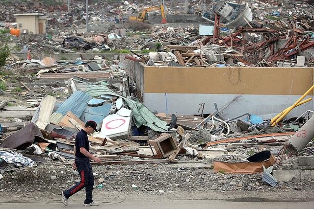 Một người đàn ông đi qua đống đổ nát ngày 12/6/2011 ở Iwate, Nhật sau một trận động đất 9,0 độ richter