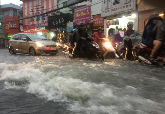 Nước mưa như vỡ đê cuồn cuồn đổ xuống dốc trên đường Võ Văn Ngân.