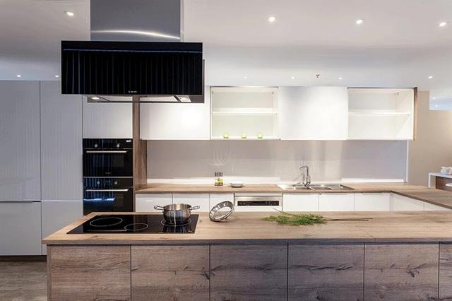Căn bếp tiện nghi, hiện đại với máy hút mùi, lò nướng kết hợp vi sóng, bếp điện từ, chậu vòi rửa.