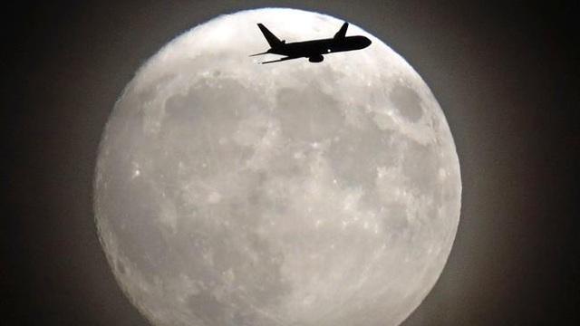 Máy bay bay trước mặt trăng khi đang tiến đến sân bay Heathrow, London (Adrian Dennis)