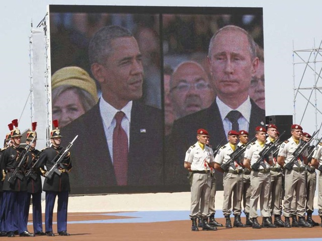 Hình ảnh Tổng thống Putin và Tổng thống Obama trên màn ảnh lớn tại lễ kỷ niệm 70 năm ngày quân đồng minh đổ bộ lên bãi biển Normandy. Ảnh: AP