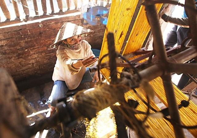 Trong những xưởng kéo tơ, các bà các chị miệt mài làm việc trong màn khói bốc nghi ngút từ nồi nước luộc kén.