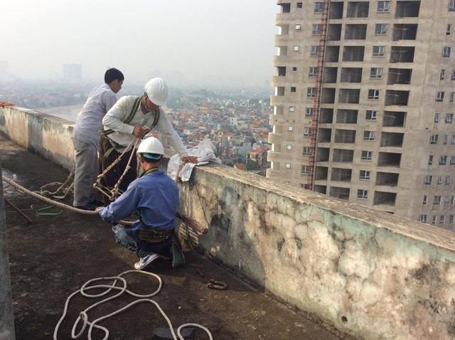 Đội công nhân chuẩn bị sơn lại mặt ngoài tòa nhà