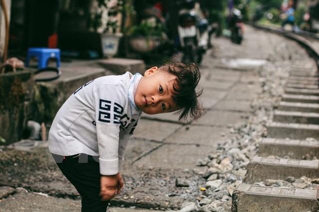 Sự hồn nhiên của đứa trẻ ngay bên cạnh con đường ẩn chứa nhiều nguy hiểm (Ảnh: Thanh Dung/Vietnam+)