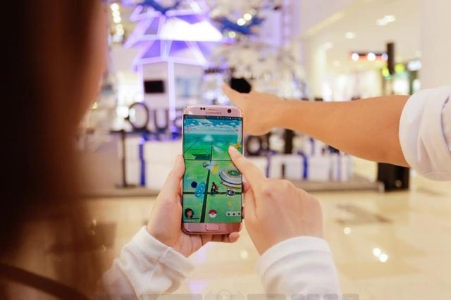 """""""Pokemon kìa, bắt liền em ơi!"""". Trung tâm thương mại vốn là nơi cư ngụ của rất nhiều cô cậu Pokemon, giờ đây lại quy tụ nhiều hơn bởi không gian Giáng sinh Galaxy của Samsung đầy ấn tượng. Nếu đang """"cày"""" tăng cấp thì hãy nhập nhóm với cặp đôi này để thu phục Pokemon nhé."""