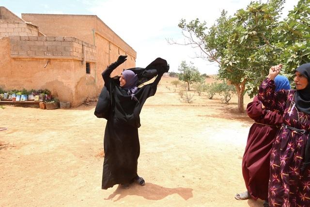 Khoảnh khắc rạng rỡ của một phụ nữ Syria khi tháo bỏ chiếc khăn trùm đầu để ăn mừng ngôi làng của cô đươc giải phóng khỏi sự chiếm đóng của tổ chức Nhà nước Hồi giáo tự xưng (IS). (Ảnh: Reuters)