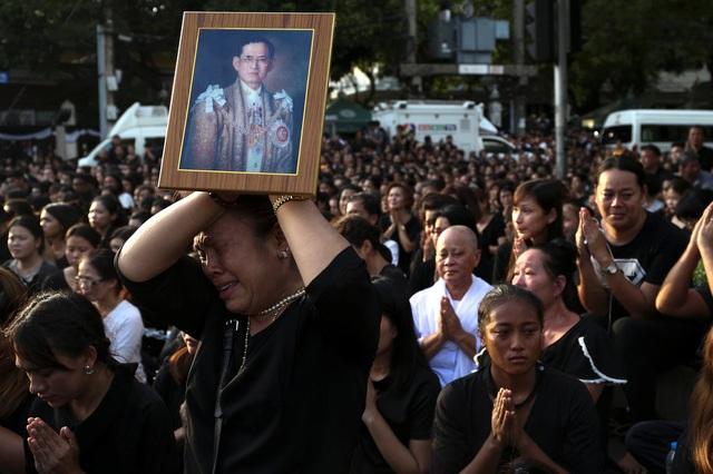Một phụ nữ òa khóc, cầm trên tay di ảnh của nhà vua Thái Lan Bhumibol Adulyadej, khi thi hài của nhà vua được chuyển từ bệnh viện - nơi ông trút hơi thở cuối cùng - về cung điện hoàng gia ở thủ đô Bangkok hôm 14/10. Quốc vương Bhumibol Adulyadej từ trần ở tuổi 88 sau 70 năm trị vì đất nước Thái Lan. (Ảnh: Reuters)