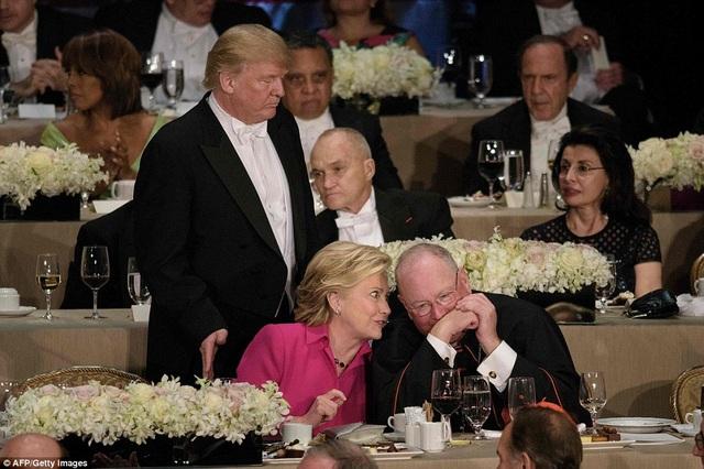 Baf Clinton nói chuyện với Đức Hồng y mà không cần để ý đến việc để ông Trump cố lách vào chỗ ngồi. (Ảnh: AFP)