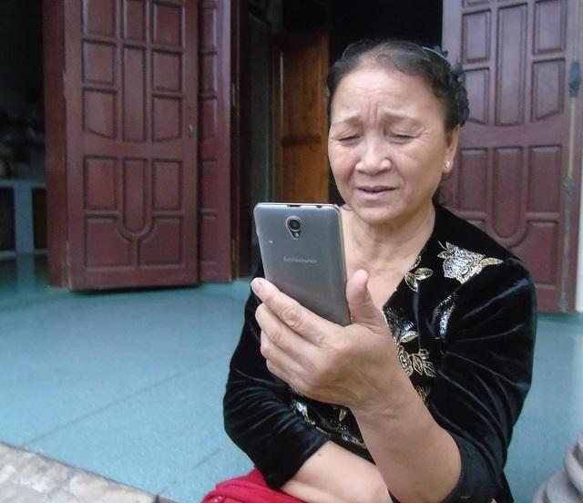 Bà Lê Thị Kỷ vui mừng khi nhận được điện thoại của con trai đang lao động tại Hàn Quốc. (Ảnh Tiến Thành)