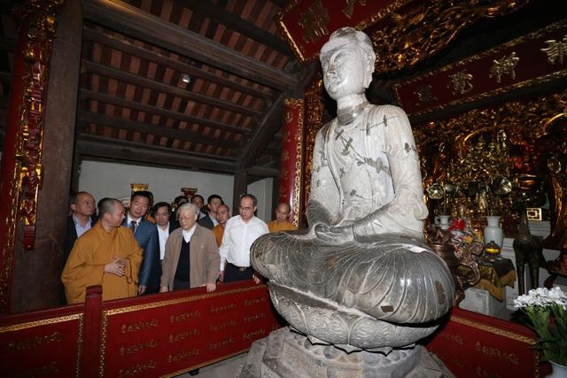 Tổng Bí thư Nguyễn Phú Trọng nghe giới thiệu Pho tượng Phật A Di Đà bằng đá (Thời Lý) , Bảo vật Quốc gia Việt Nam tại chùa Phật Tích. Ảnh: Trí Dũng– TTXVN