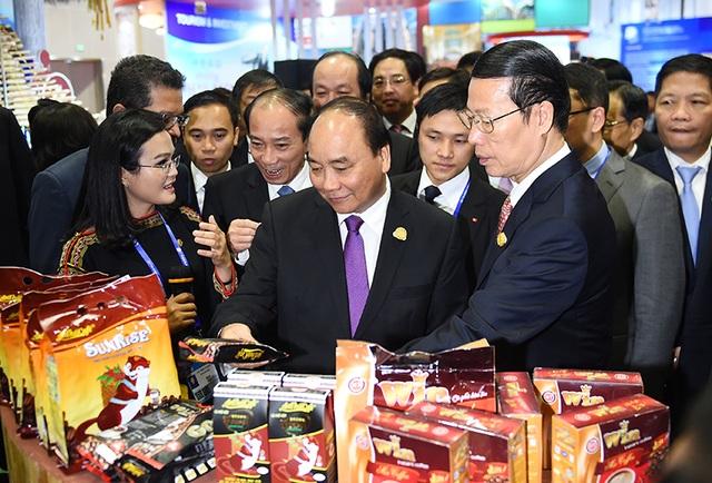 Thủ tướng Nguyễn Xuân Phúc cùng Phó Thủ tướng Trung Quốc Trương Cao Lệ tham quan gian hàng cà phê của Việt Nam.