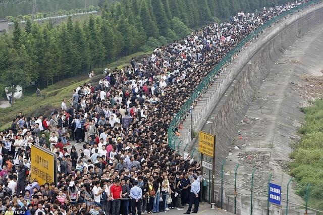 Hàng nghìn người xếp hàng vây quanh khu vực bờ sông Tiền Đường ở Hàng Châu, tỉnh Chiết Giang năm 2010 để chờ xem thủy triều. (Ảnh: Reuters)