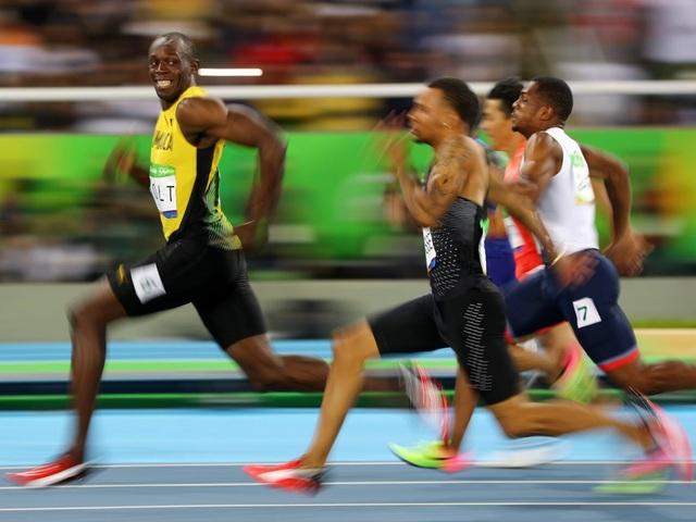 Khoảnh khắc vận động viên điền kinh Usain Bolt của Jamaica nở nụ cười khi đang trên đường đua cùng các đối thủ trong trận bán kết chạy 100m nam tại Thế vận hội Olympic Rio 2016 tại Rio de Janeiro, Brazil ngày 14/8. (Ảnh: Reuters)