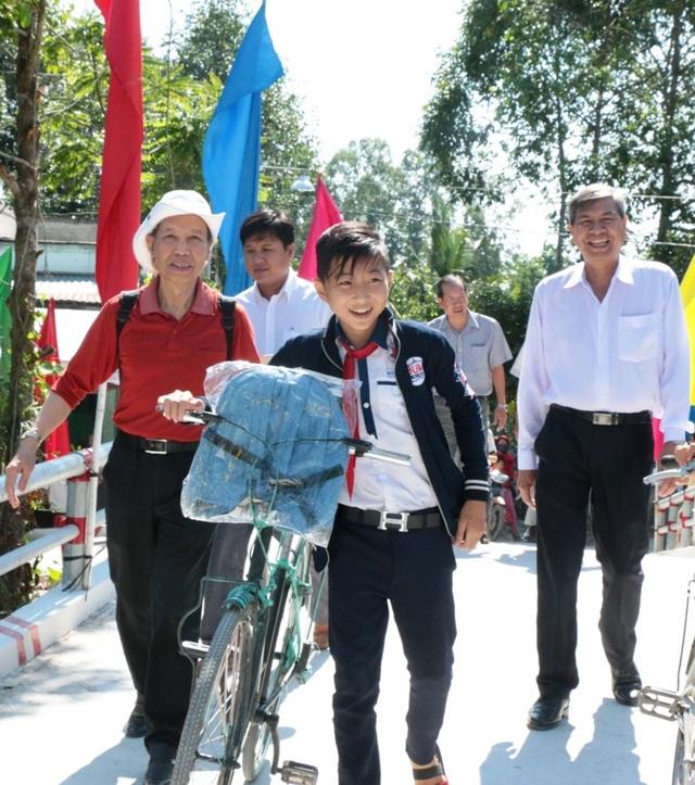 Niềm vui của các em học sinh, người dân, Tổng biên tập báo Dân trí Phạm Huy Hoàn và đồng chí Chủ tịch UBND huyện Lai Vung Hồ Thanh Phương đi qua cầu Dân trí