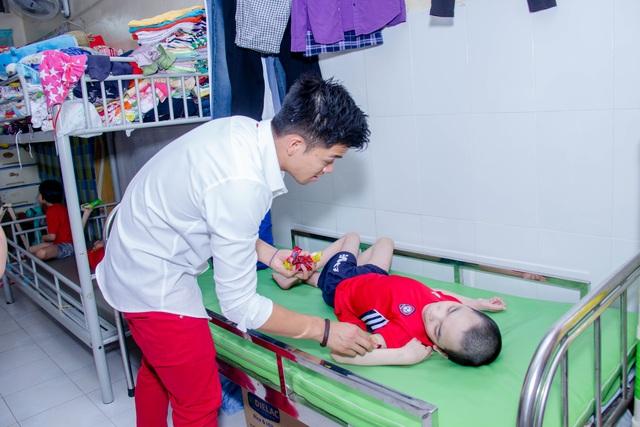 Nụ cười của nam ca sĩ khi được trao quà cho một em nhỏ và anh cũng đi đến từng giường để trao quà cho các em không thể đi lại.