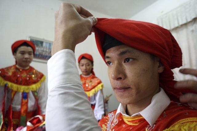 Đội múa năm nay gồm 12 người nam đều là người gốc Triều Khúc, người trẻ nhất mới chỉ 14 tuổi. Trong ảnh là thao tác chít khăn mỏ quạ được trùm ra ngoài khăn xếp khi đội múa hóa trang chuẩn bị tham gia đám rước.