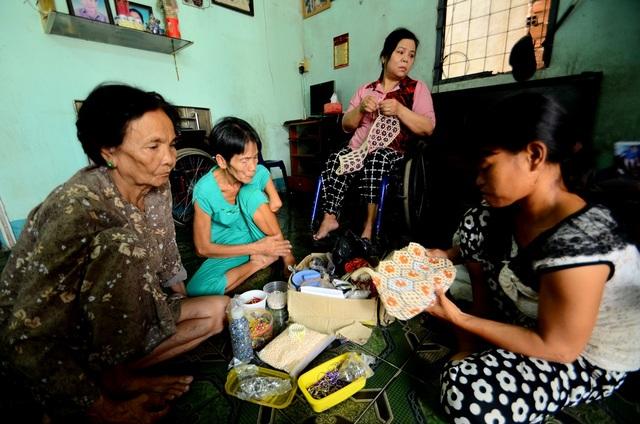 Các thành viên trong gia đình chị Thương đang gia công kết cườm.