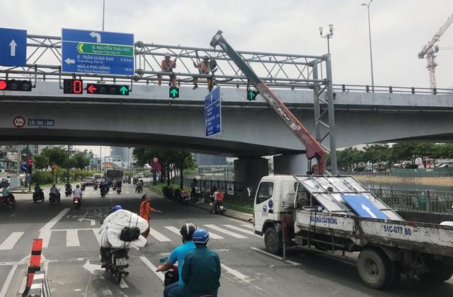 Các công nhân đang thi công thay thế, lắp bổ sung biển chỉ đường bằng tiếng Anh tại giao lộ Võ Văn Kiệt - Nguyễn Thái Học, sáng 20/5.