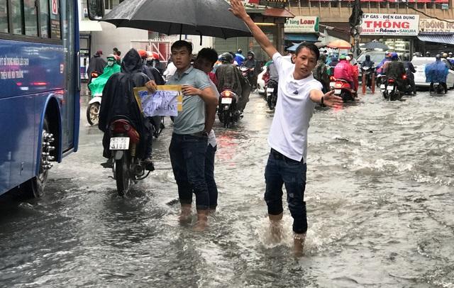 Mặt đường đầy hố sâu nguy hiểm trong cơn mưa, nhiều thanh niên địa phương đã xuống đường cảnh báo người dân.