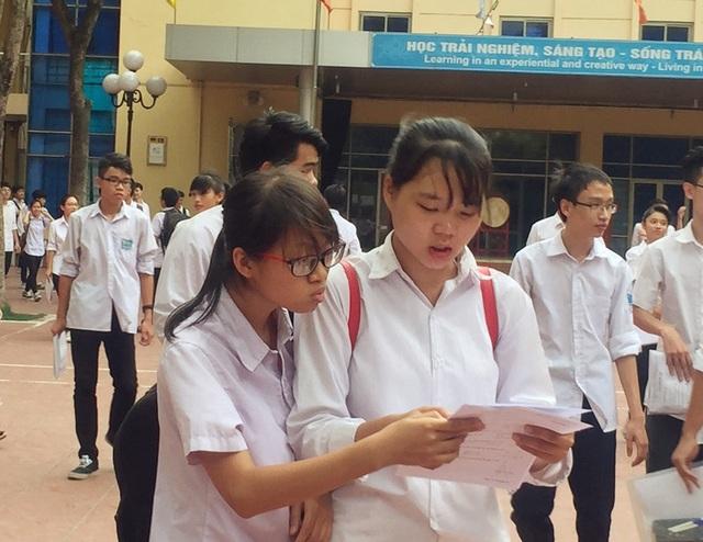 Thí sinh xem lại đề Toán sau khi rời phòng thi ở điểm trường THPT Lômônôxốp, Hà Nội. (Ảnh: Lệ Thu)