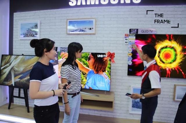 Khách hàng trải nghiệm TV QLED Samsung và được tư vấn mua sắm trong Tuần lễ vàng Samsung tại Nguyễn Kim