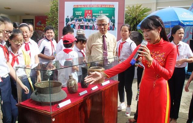 Các em học sinh chăm chú lắng nghe giới thiệu về các kỷ vật kháng chiến của các Liệt sĩ, Mẹ Việt Nam anh hùng.
