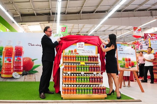 Đại diện THFC, ông Wolfgang Friess- Tổng Giám đốc Công ty cổ phần Chuỗi thực phẩm TH và đại diện BigC, bà Phạm Huyền Trang kéo rèm đỏ giới thiệu sản phẩm mới TH true Herbal tại siêu thị Big C Thăng Long