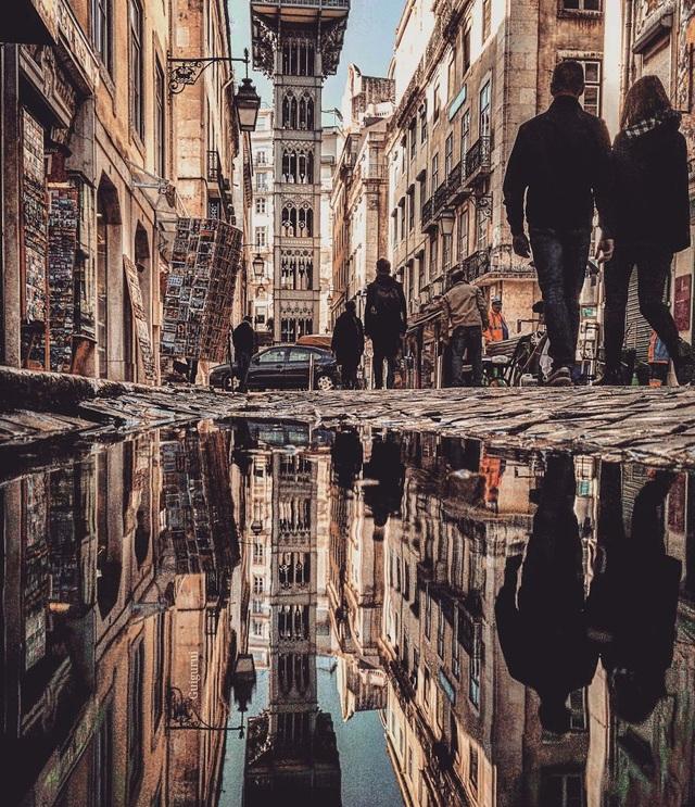 Vũng nước mưa tái hiện lại hoàn hảo hình ảnh các tòa nhà và người đi bộ tại thành phố Lisbon, Bồ Đào Nha.