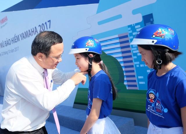 Ông Khuất Việt Hùng - Phó Chủ tịch chuyên trách Ủy ban ATGT Quốc gia hướng dẫn một em học sinh cách đội MBH an toàn