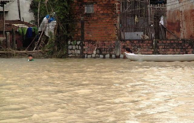 Dù nước lũ còn sâu nhưng 2 chị em nhỏ này như chẳng biết sợ vẫn liều mình lội lũ về nhà.