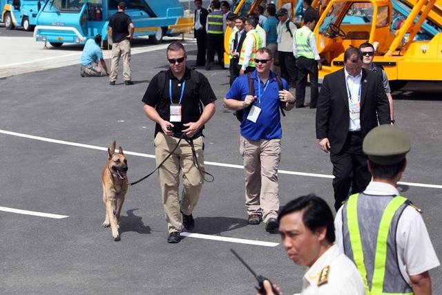 Đặc vụ Mỹ mang theo chó nghiệp vụ rà soát một số điểm quanh vị trí dự kiến đón máy bay Tổng thống Mỹ.