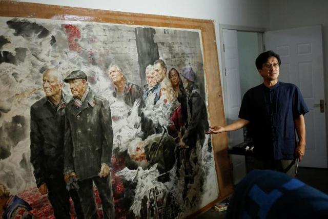 """Những năm gần đây, nhu cầu về các tác phẩm nghệ thuật Triều Tiên có dấu hiệu tăng trưởng ở Trung Quốc. Park Young-jeong, một nhà nghiên cứu thuộc Học viện Văn hóa và Du lịch Hàn Quốc cho biết: """"Người Trung Quốc đã bắt đầu có thú vui sưu tầm nghệ thuật và họ có thể mua những tác phẩm nghệ thuật Triều Tiên dễ dàng hơn với giá thành rẻ hơn"""". Trong ảnh: Người đứng đầu Bảo tàng Nghệ thuật Mansudae Ji Zhengtai giới thiệu về một bức tranh của một nghệ sỹ Triều Tiên tại phòng tranh ở Bắc Kinh, Trung Quốc."""