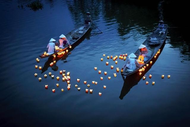 Các cô gái trong áo dài áo dài truyền thống ở thành phố Huế thả những ngọn nến nổi trên sông để cầu nguyện cho người đã khuất. Thả hoa đăng là một trong các phong tục truyền thống tại các quốc gia Phật giáo như Việt Nam. (Click vào đây để xem ảnh kích thước lớn)