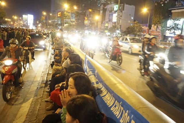 Một lượng người đến muộn phải ngồi tại giải lan can phân cách của cầu vượt Ngã Tư Sở.