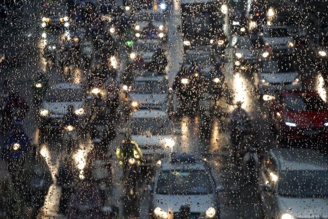 Dòng người rời công sở về trong cơn mưa.