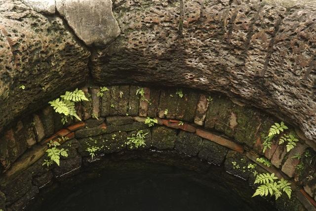 Bên trong giếng, các lớp gạch xếp chồng lên nhau dưới phần cổ giếng bằng đá ong.
