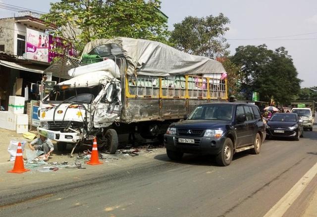 Chiếc xe tải biển số Lào bị xe đầu kéo tông bẹp cabin, tài xế bị thương nặng.