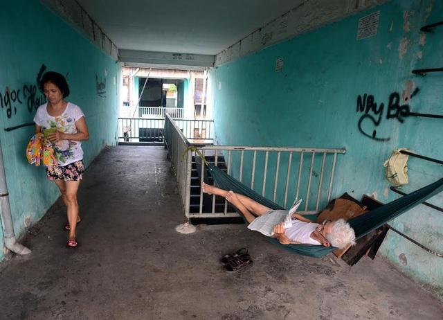 Một cụ ông phải mắc võng ngoài hành lang nằm đọc báo vì nhà diện tích nhỏ lại đông người chen chúc.