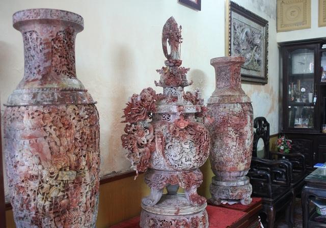 """Đây là bộ tác phẩm được làm hoàn toàn bằng đá tự nhiên gồm một Lư Hương có đường kính 45cm, cao 118cm được chạm khắc bối cảnh """"lưỡng long tranh châu"""" và đôi lọ hoa có đường kính 40cm, cao 108cm được chạm khắc cảnh sinh hoạt của người Việt cổ."""
