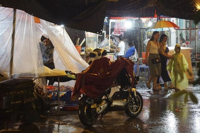 Một cơn mưa ập xuống khiến nhiều cửa hàng phải căng nilon che mưa...