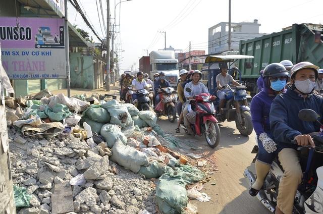 Người dân vô ý thức đổ vật liệu, xà bần ra đường góp phần làm tình trạng kẹt xe thêm trầm trọng