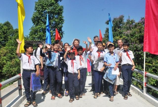 Tổng biên tập báo Dân trí Phạm Huy Hoàn cùng đại biểu, các em học sinh vui mừng đi qua cầu Dân trí
