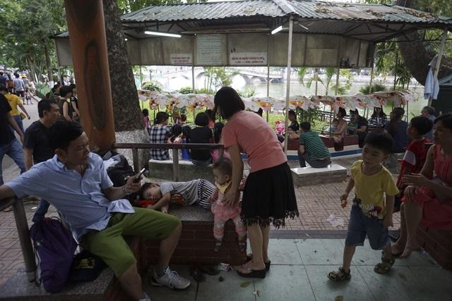 Một gia đình có trẻ nhỏ kiếm tạm được chỗ trống tranh thủ nghỉ ngơi.