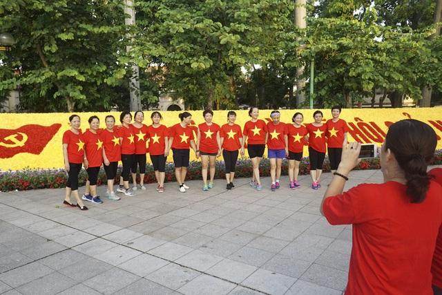 Những người tập thể dục buổi sáng bên đường Điện Biên Phủ mặc áo Cờ đỏ sao vàng trong buổi sáng ngày Quốc khánh.