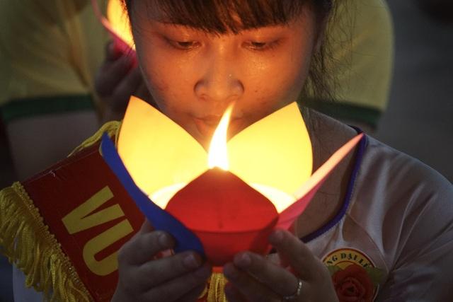 Giây phút thành kính của một nữ thanh niên với ngọn nến tri ân trên tay.