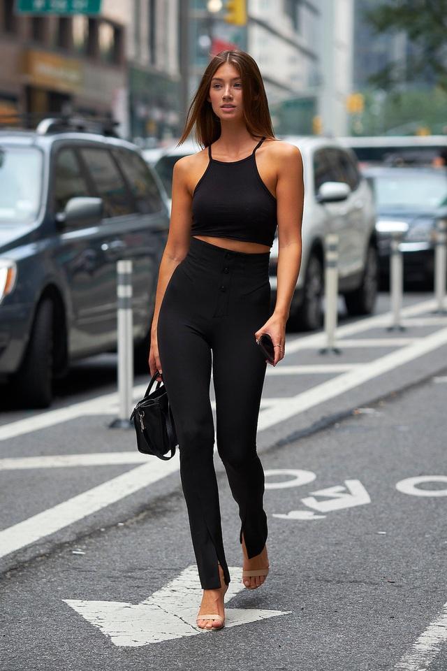 Người mẫu Đức Lorena Rae mặc quần cạp cao, áo crop top gợi cảm, khoe bờ vai và vòng eo. Rae cũng dùng chiếc túi xách nhỏ màu đen, tạo vẻ đẹp nhẹ nhàng, chuyên nghiệp.